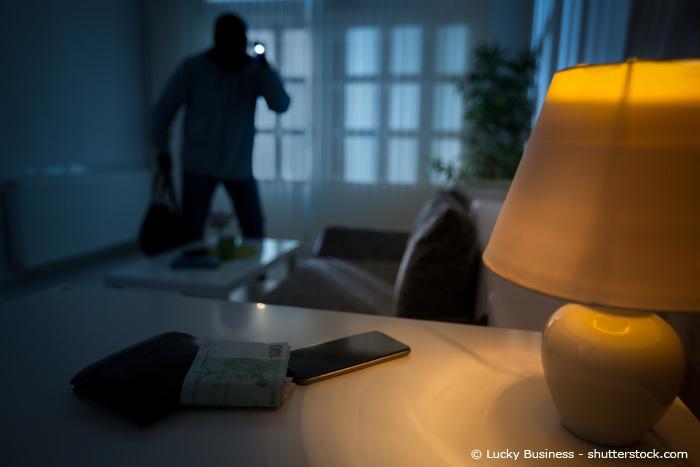 Einbrecher mit Taschenlampe im Haus