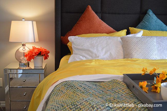 Bunte Decken und Kissen bringen den Frühling ins Schlafzimmer.